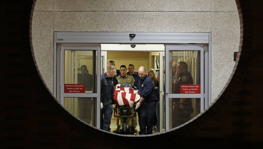 The body of a Kittitas County Sheriff's deputy is draped with a U.S. flag as it is carried out of Kittitas Valley Healthcare Hospital, in the early morning hours of Wednesday, March 20, 2019, in E ...
