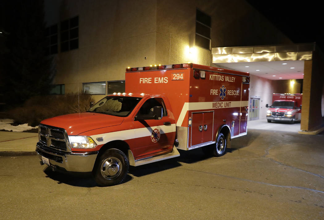 A Kittitas Valley Fire & Rescue ambulance carries the body of a Kittitas County Sheriff's deputy away from Kittitas Valley Healthcare Hospital, in the early morning hours of Wednesday, March 2 ...