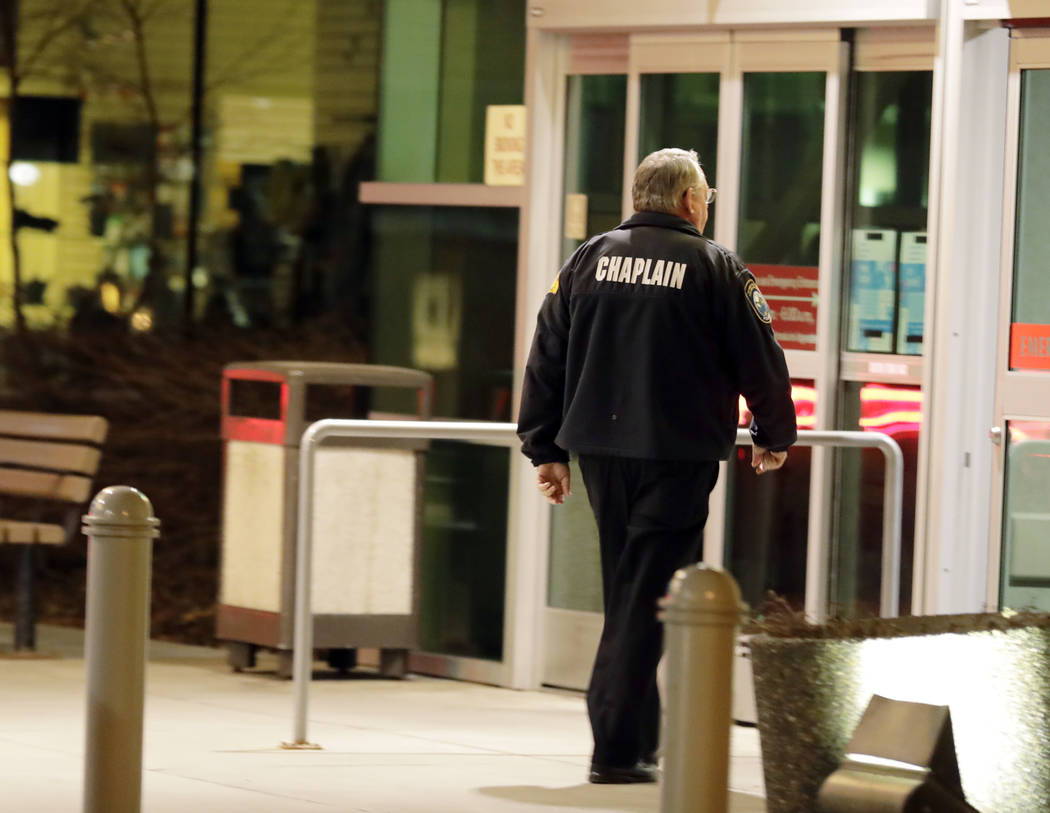 A law enforcement chaplain walks into Kittitas Valley Healthcare Hospital, in the late night hours of Tuesday, March 19, 2019, in Ellensburg, Wash., prior to a procession to accompany the body of ...