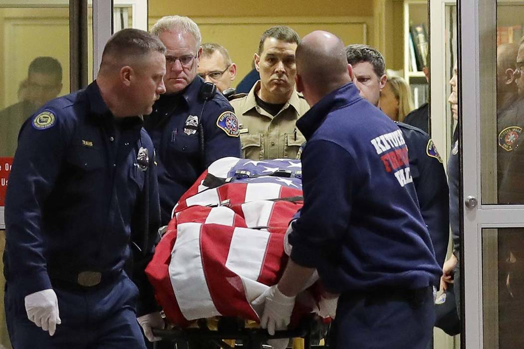 The body of a Kittitas County Sheriff's deputy is draped with a U.S. flag as it is carried out of Kittitas Valley Healthcare Hospital in the early morning hours of Wednesday, March 20, 2019, in El ...
