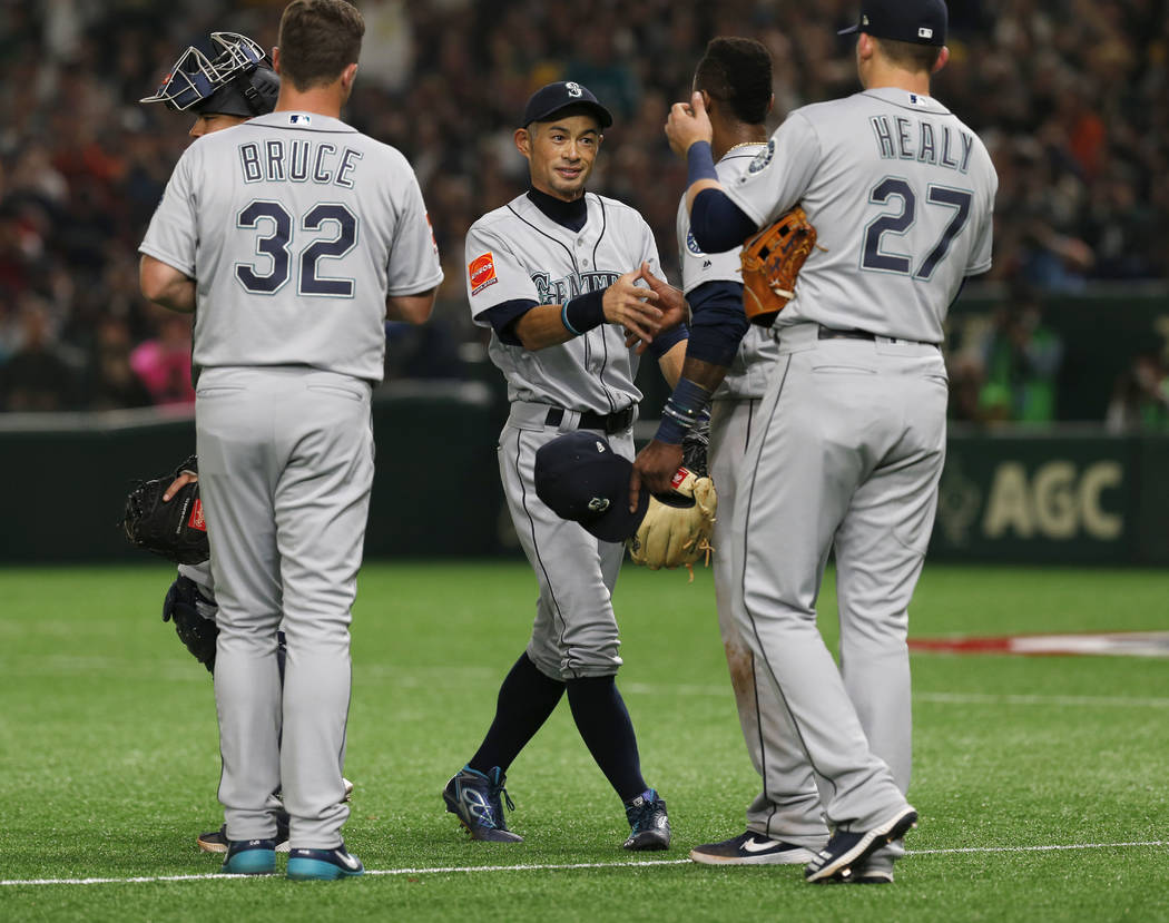Seattle Mariners right fielder Ichiro Suzuki, center, talks to his teammates while leaving the field for defense substitution in the fourth inning of Game 1 of the Major League opening baseball se ...