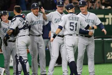 Seattle Mariners right fielder Ichiro Suzuki (51) celebrates with teammates after defeating the Oakland Athletics 9-7 in Game 1 of their Major League opening series baseball game at Tokyo Dome in ...