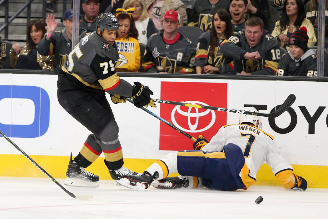 Vegas Golden Knights right wing Ryan Reaves (75) knocks down Nashville Predators defenseman Yannick Weber (7) during the first period of an NHL hockey game at T-Mobile Arena in Las Vegas, Saturday ...