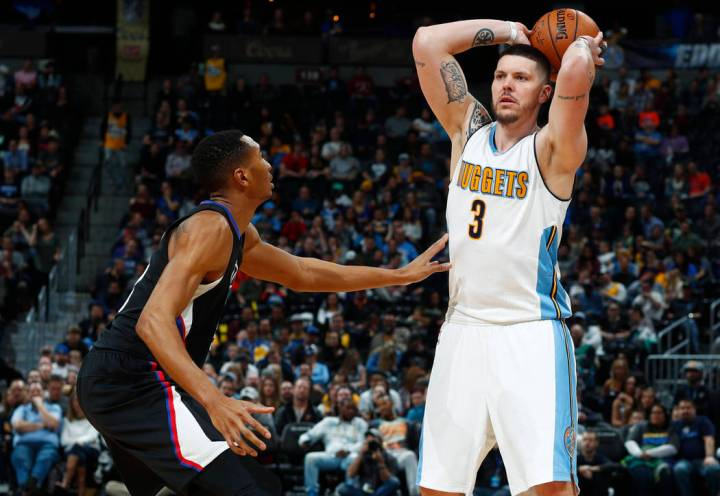 Los Angeles Clippers forward Wesley Johnson, left, defends as Denver Nuggets guard Mike Miller looks to pass the ball late in the second half of an NBA basketball game Saturday, Jan. 21, 2017, in ...