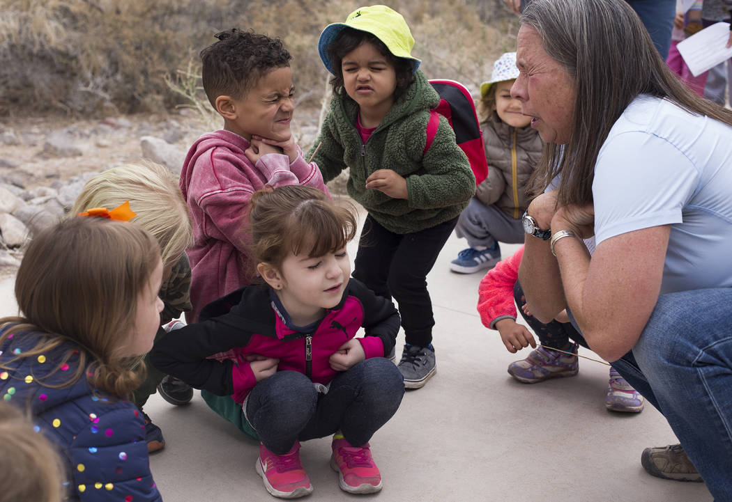 Naturalist Jody Walker shows Alina Velaochaga, 4, from left, Asante Ricigliano-Vaughn, 5, and Louie Schmidt, 3, how to pretend to be a baby owl during the Nature Tykes program at Clark County Wetl ...