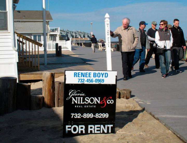 FILE- In this March 8, 2014 file photo people walk past a home being offered as a summer rental on the boardwalk in Point Pleasant Beach N.J. New Jersey shore property owners and renters worry tha ...