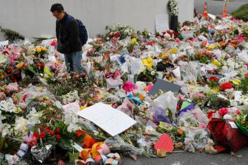 Mourners lay flowers near the Al Noor mosque in Christchurch, New Zealand, Thursday, March 21, 2019. (AP Photo/Vincent Thian)