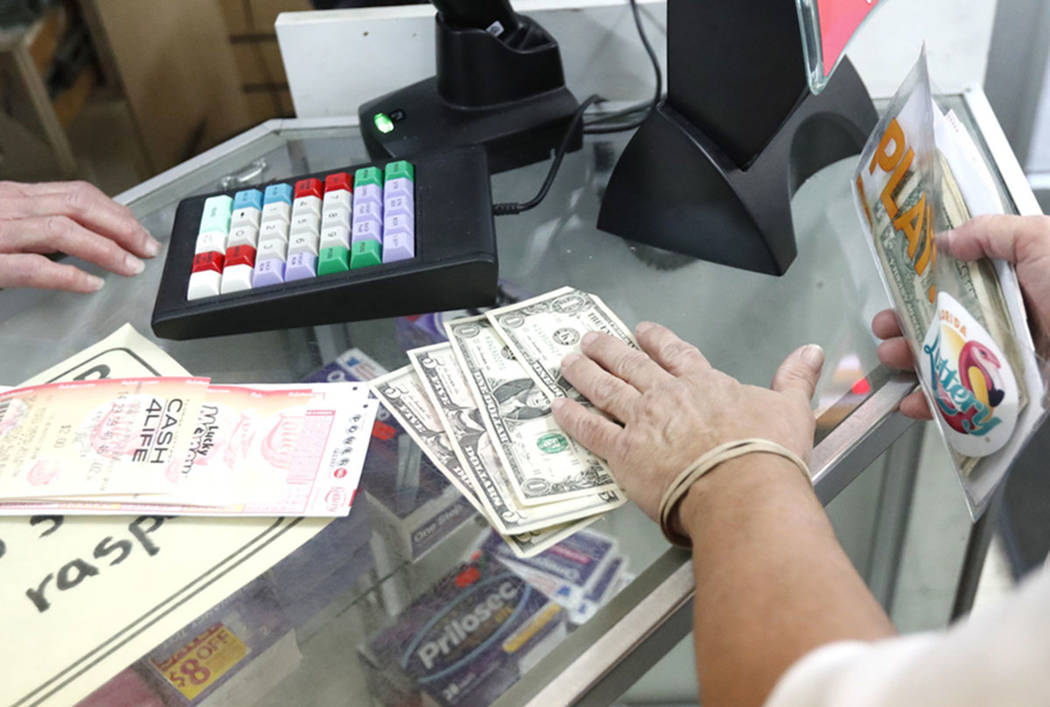 A customer purchases lottery tickets at La Preferida Superdiscount store in Hialeah, Fla., in 2018. (AP Photo/Wilfredo Lee)