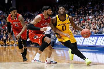 Arizona State's Luguentz Dort (0) drives against St. John's Marvin Clark II, center, during the first half of a First Four game of the NCAA men's college basketball tournament Wednesday, March 20, ...