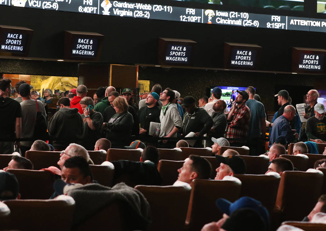 Fans lined up to place their bets as others watch a basketball game during the first day of the NCAA basketball tournament at the Westgate sports book in Las Vegas on Thursday, March 16, 2019. (Bi ...