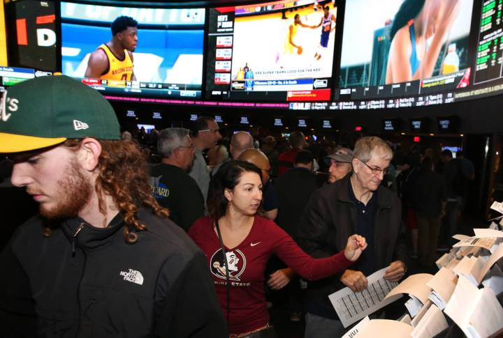 Fans, including Ivette Abramyan, center, of Jacksonville, Fla,., lined up to place their bets during the first day of the NCAA basketball tournament at the Westgate sports book in Las Vegas on Thu ...