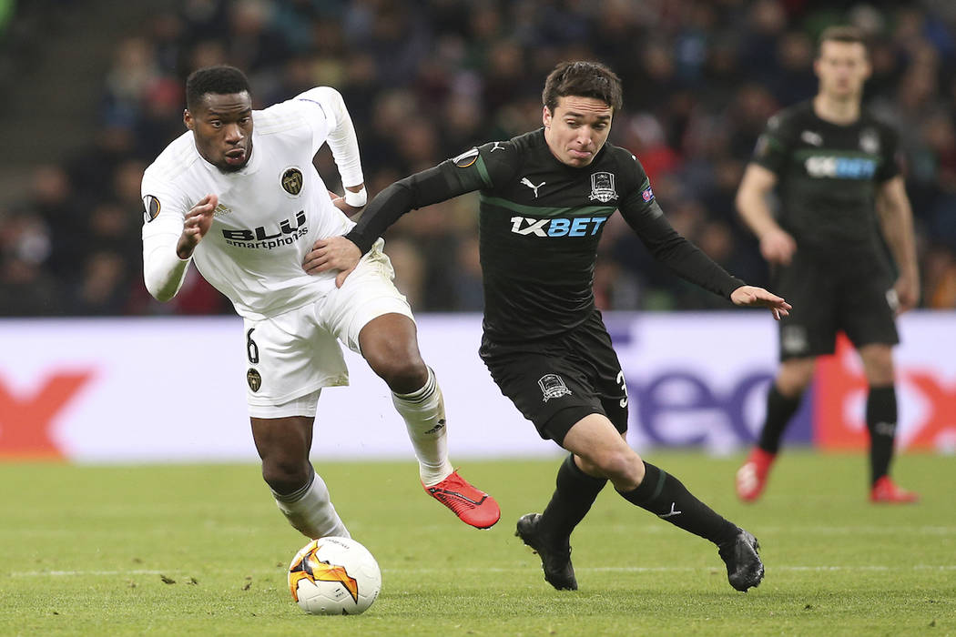 Valencia's Geoffrey Kondogbia, left, and Krasnodar's Mauricio Pereyra challenge for the ball during the Europa League round of 16, second leg soccer match between FC Krasnodar and Valencia at the ...