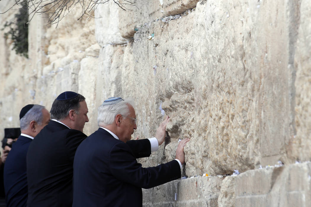 Israeli Prime Minister Benjamin Netanyahu, U.S. Secretary of State Mike Pompeo and U.S. Ambassador to Israel David Friedman touch the stones of the Western Wall during a visit to the site in Jerus ...