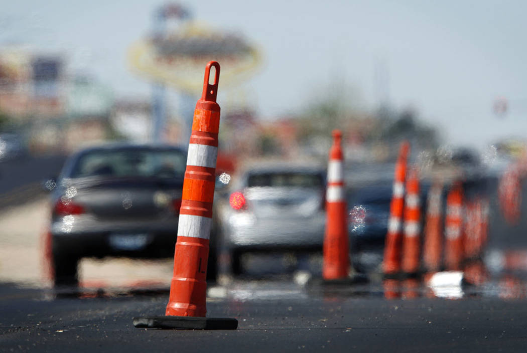 Heat rising from the pavement distorts the images of cars as they drive through road construction. (Las Vegas Review-Journal)