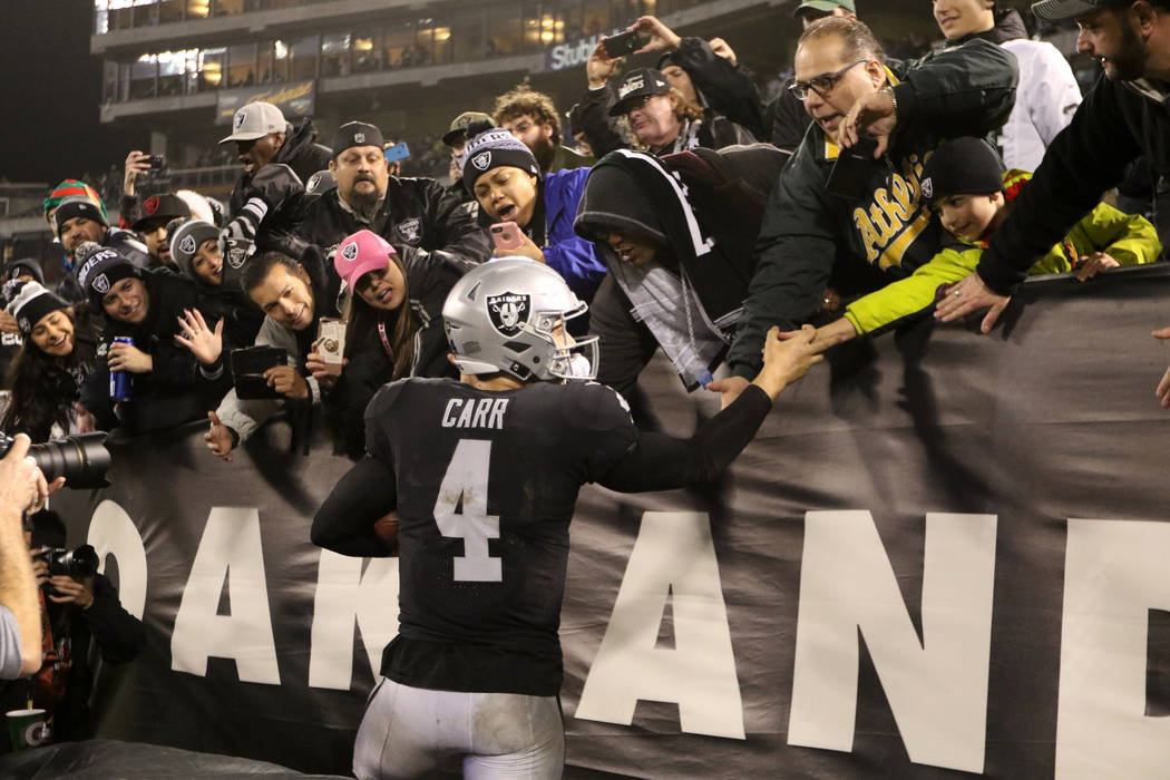 Oakland Raiders quarterback Derek Carr (4) meets with fans the Oakland-Alameda County Coliseum field after the team's win over the Denver Broncos in Oakland, Calif., Monday, Dec. 24, 2018. Heidi F ...