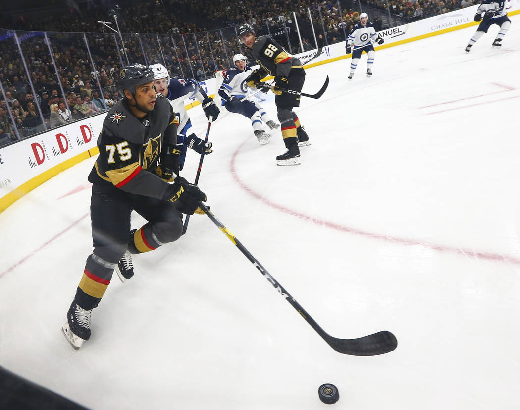 Golden Knights right wing Ryan Reaves (75) moves the puck past Winnipeg Jets defenseman Tyler Myers (57) during the first period of an NHL hockey game at T-Mobile Arena in Las Vegas on Thursday, M ...