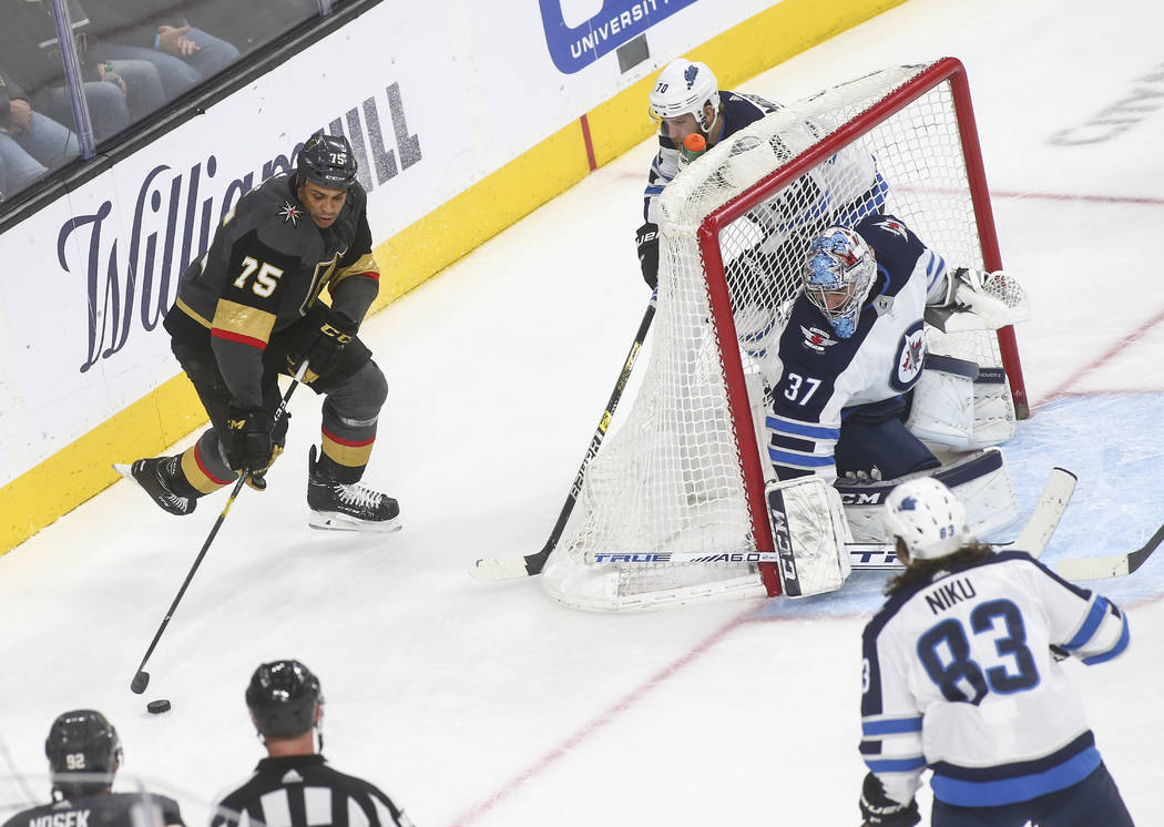 Golden Knights right wing Ryan Reaves (75) moves the puck around Winnipeg Jets defenseman Joe Morrow (70) and goaltender Connor Hellebuyck (37) during the third period of an NHL hockey game at T-M ...