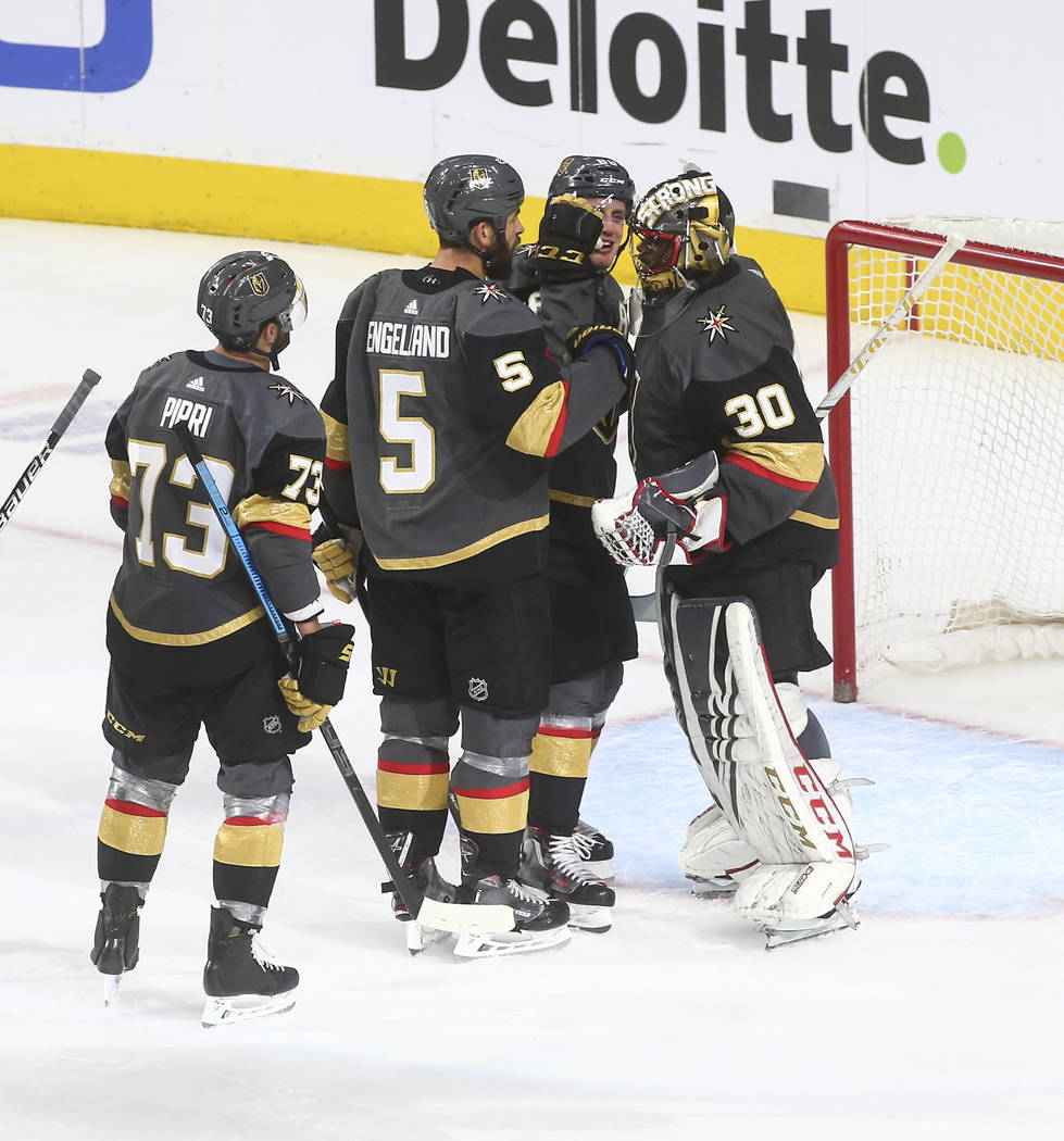 Golden Knights defensemen Deryk Engelland (5) and Nate Schmidt celebrate a shutout victory with goaltender Malcolm Subban (30) after the team won 5-0 against the Winnipeg Jets an NHL hockey game a ...