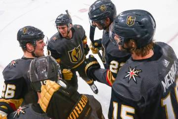 Golden Knights players, from left, Paul Stastny (26), Jonathan Marchessault, Nick Holden, and Jon Merrill celebrate a goal by Reilly Smith, lower left, during the first period of an NHL hockey gam ...