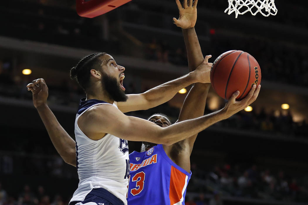 Nevada forward Caleb Martin drives to the basket past Florida center Kevarrius Hayes, rear, during a first round men's college basketball game in the NCAA Tournament, Thursday, March 21, 2019, in ...