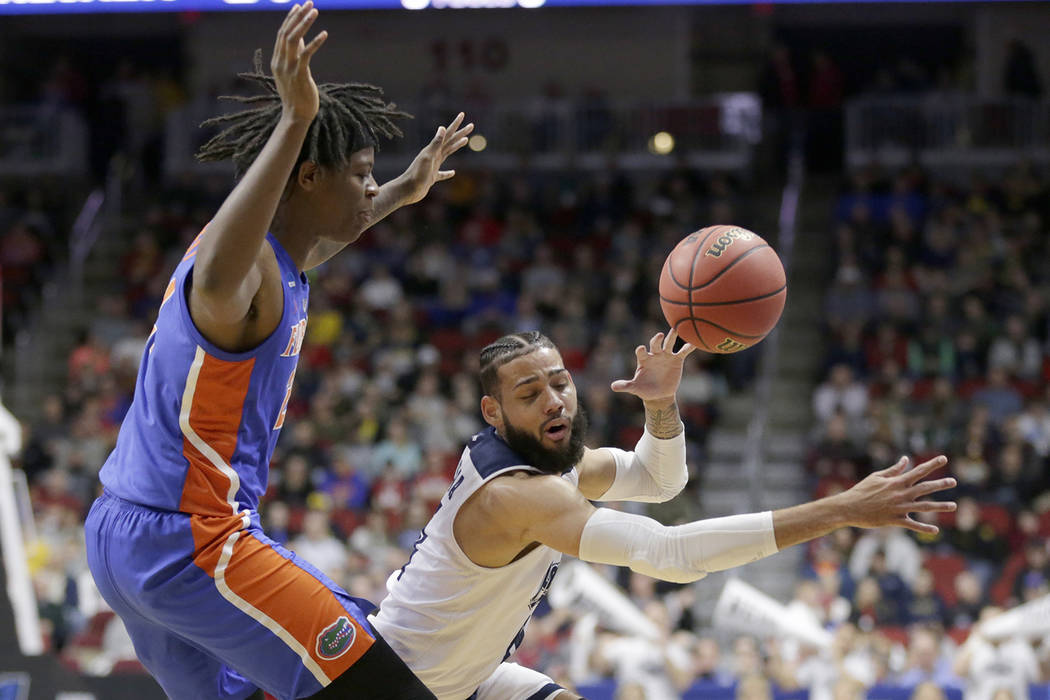 Nevada's Cody Martin, right, loses control of the ball as he drives around Florida's Andrew Fava, left, during the first half of a first round men's college basketball game in the NCAA Tournament ...