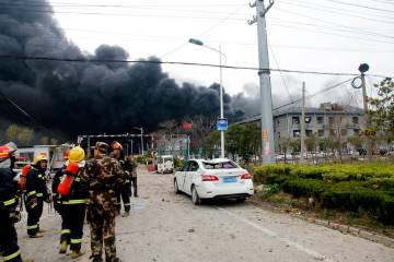 In this Thursday, March 21, 2019, photo, rescuers walk near the site of a factory explosion in a chemical industrial park in Xiangshui County of Yancheng in eastern China's Jiangsu province. The l ...
