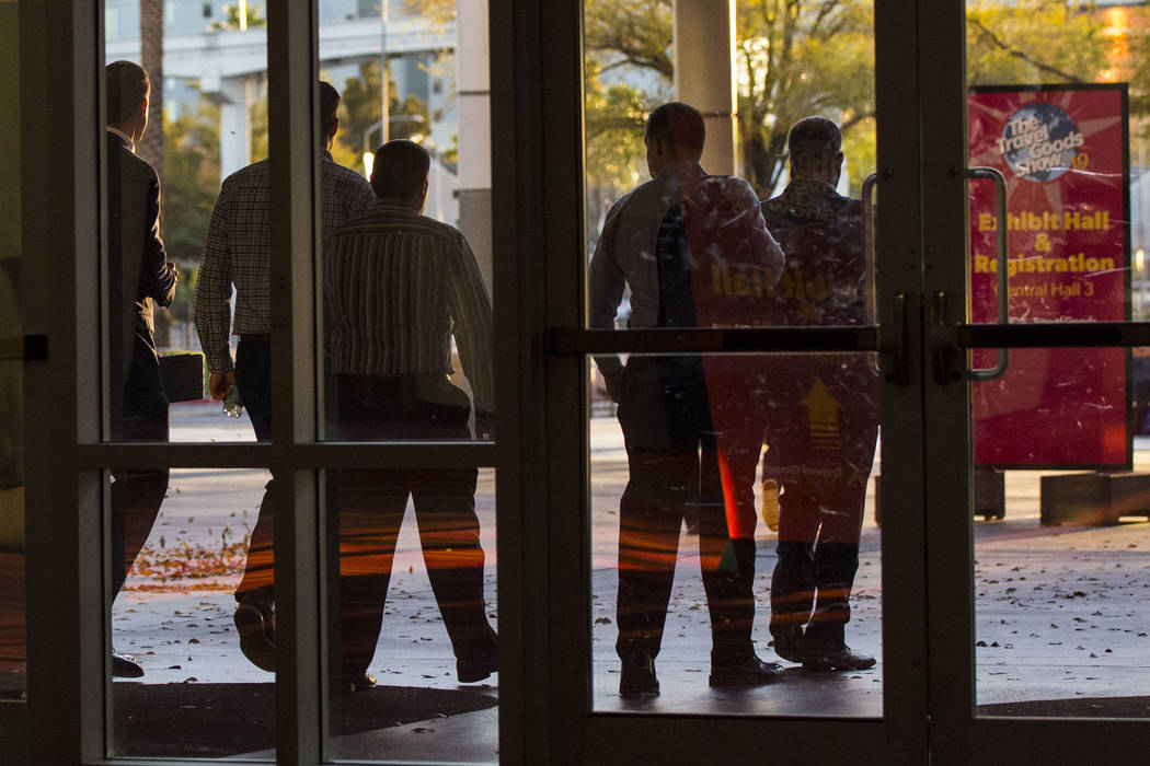 Plainclothes Las Vegas police officers walk out of the Las Vegas Convention Center after execut ...