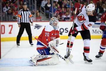 Washington Capitals goaltender Braden Holtby (70) tries to corral the puck, next to New Jersey Devils center Blake Coleman (20) during the first period of an NHL hockey game Friday, March 8, 2019, ...