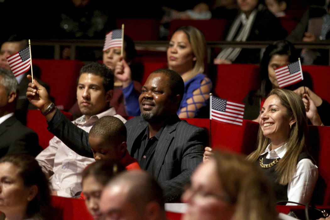 """New U.S. citizen Felix Odeh, of Nigeria, (center) and other new citizens wave American flags as """"God Bless America"""" is sung during a naturalization ceremony at the George W. Bush Preside ..."""