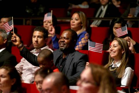 "New U.S. citizen Felix Odeh, of Nigeria, (center) and other new citizens wave American flags as ""God Bless America"" is sung during a naturalization ceremony at the George W. Bush Preside ..."
