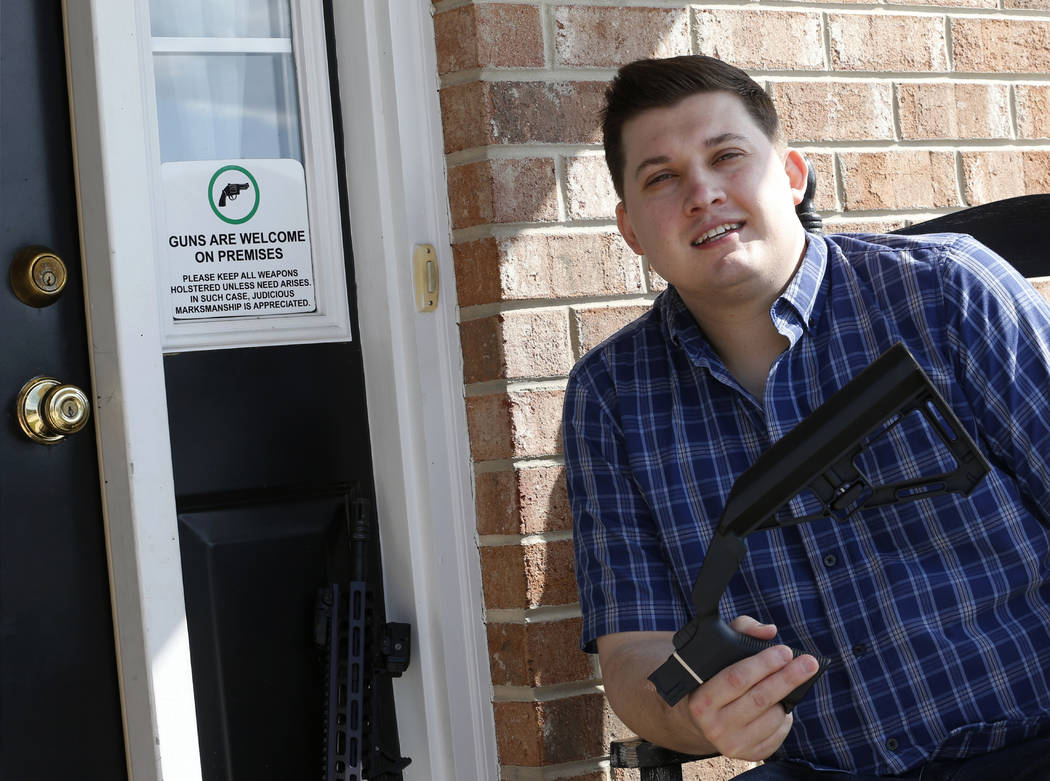 In this March 15, 2019 photo, Ryan Liskey displays a bump stock on the front porch of his home in Harrisonburg, Va. The ban on bump stocks is just a few days away and owners of the devices like Li ...