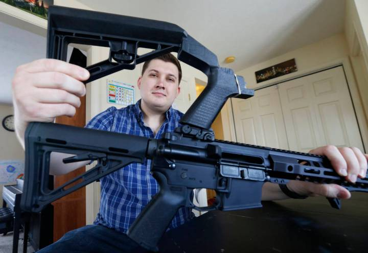 In this March 15, 2019 photo, Ryan Liskey displays a bump stock on top of his AR-15 at his home in Harrisonburg, Va. The ban on bump stocks is just a few days away and owners of the devices like L ...