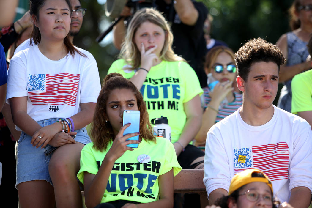 Kelly Choi, 17, from left, Franlisha Vasquez, 15, and Amit Dadon watch Manny Oliver create a mural at a Road to Change Voter Registration Walk at Sunset Park in Las Vegas, Monday, July 16, 2018. T ...