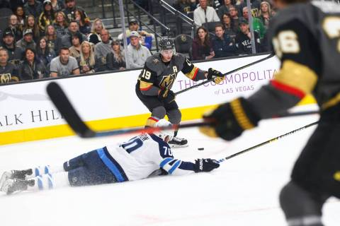 Winnipeg Jets defenseman Joe Morrow (70) falls to the ice as Golden Knights right wing Reilly Smith (19) lines up the puck to score the team's second goal against the Jets during the first period ...