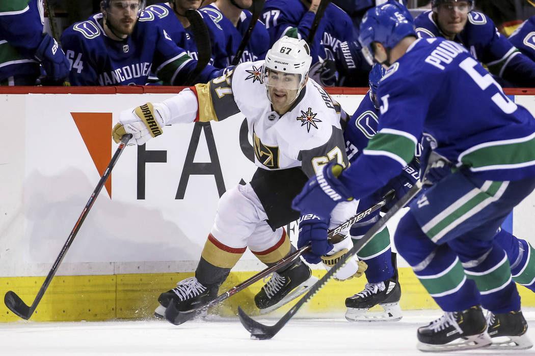 Vegas Golden Knights  Max Pacioretty (67) fights for the puck against  Vancouver Canucks 70cd7d825