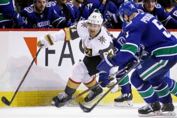 Vegas Golden Knights' Max Pacioretty (67) fights for the puck against Vancouver Canucks' Derrick Pouliot (5) during the second period of an NHL hockey game in Vancouver, British Columbia, Saturday ...