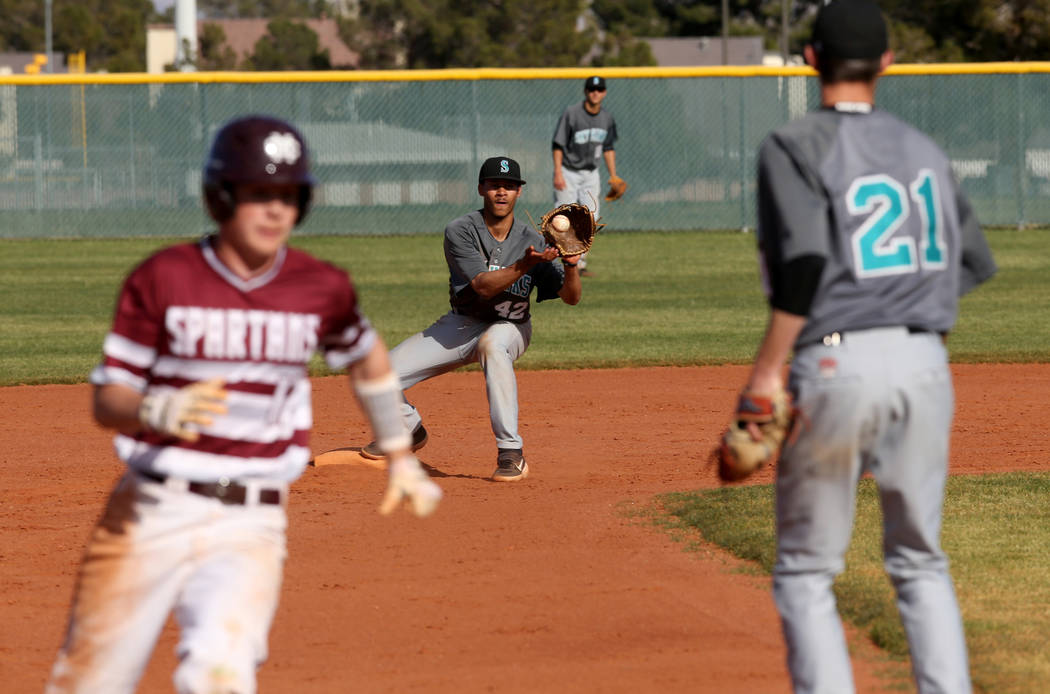 Silverado's Seton Cifelli (21) throws to second baseman Caleb Hubbard (42) to get one out of an attempted double play as Cimarron-Memorial baserunner Anthony Ortiz (12) rounds third base in the th ...