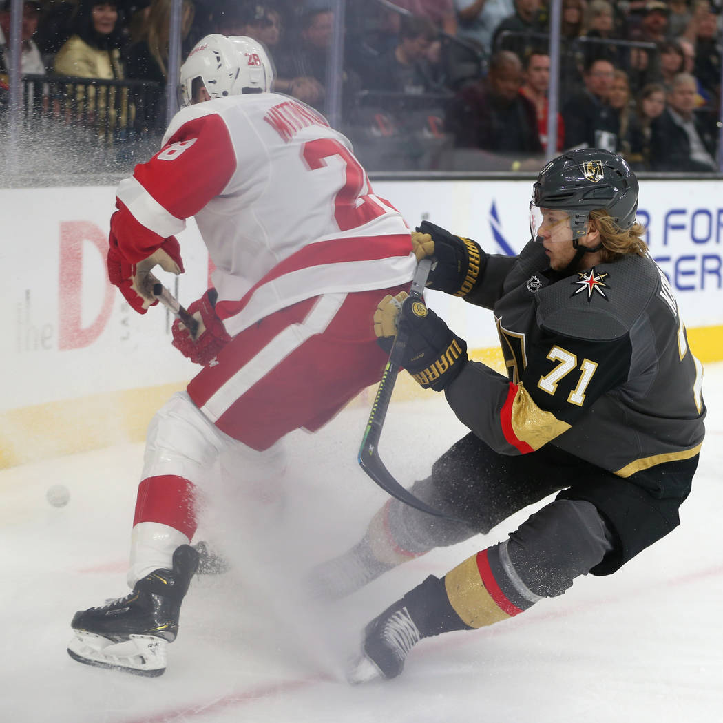Vegas Golden Knights center William Karlsson (71) fights for the puck against Detroit Red Wings right wing Luke Witkowski (28) during the first period of an NHL hockey game at T-Mobile Arena in La ...