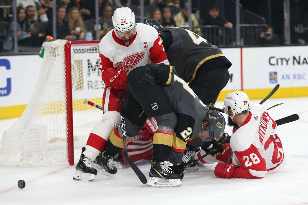 Vegas Golden Knights center Cody Eakin (21) fights for the puck against Detroit Red Wings defenseman Brian Lashoff (32) during the first period of an NHL hockey game at T-Mobile Arena in Las Vegas ...