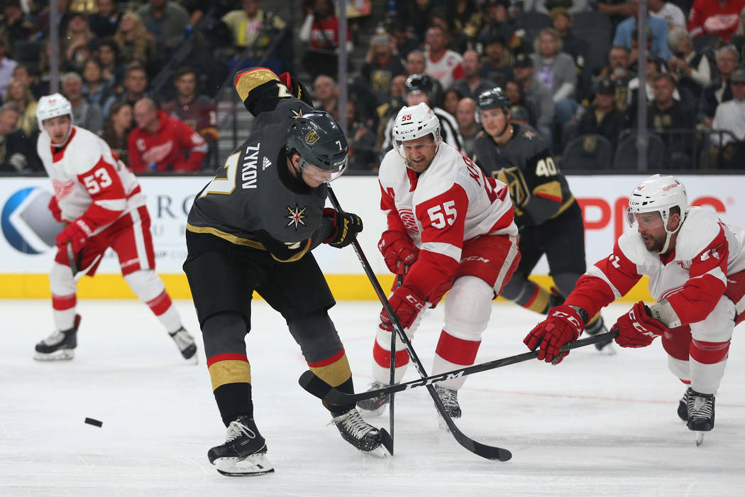 Vegas Golden Knights left wing Valentin Zykov (7) goes for the puck against Detroit Red Wings defenseman Niklas Kronwall (55) and center Luke Glendening (41) during the second period of an NHL hoc ...