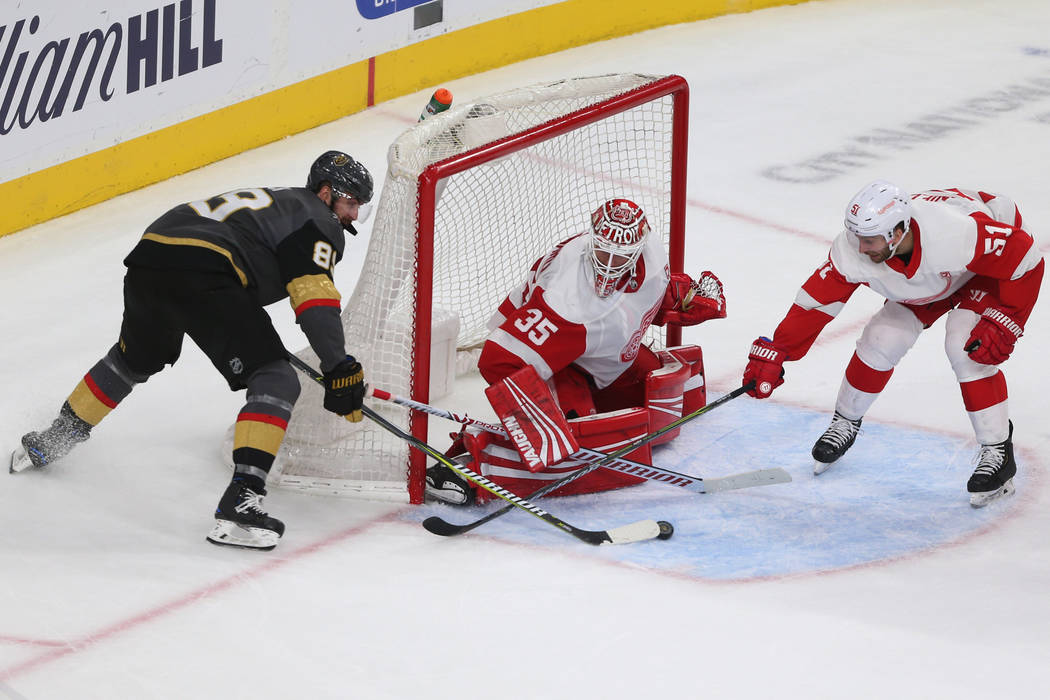 Vegas Golden Knights right wing Alex Tuch (89) fights for the puck against Detroit Red Wings center Frans Nielsen (51) and goaltender Jimmy Howard (35) during the third period of an NHL hockey gam ...