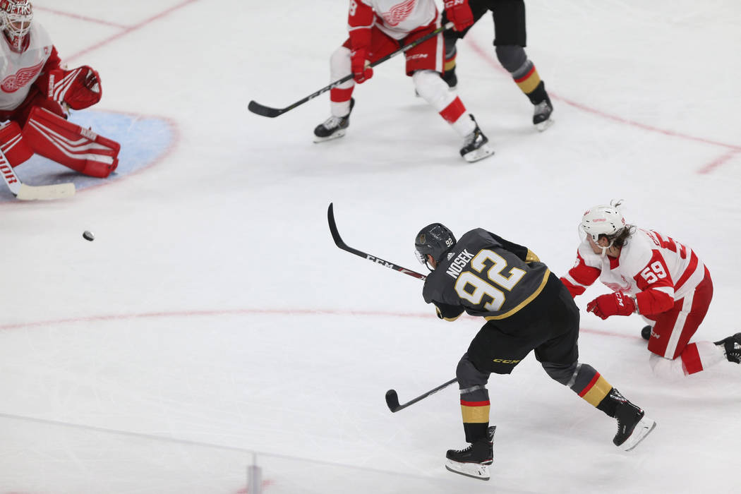 Vegas Golden Knights left wing Tomas Nosek (92) takes a shot under pressure from Detroit Red Wings left wing Tyler Bertuzzi (59) during the third period of an NHL hockey game at T-Mobile Arena in ...