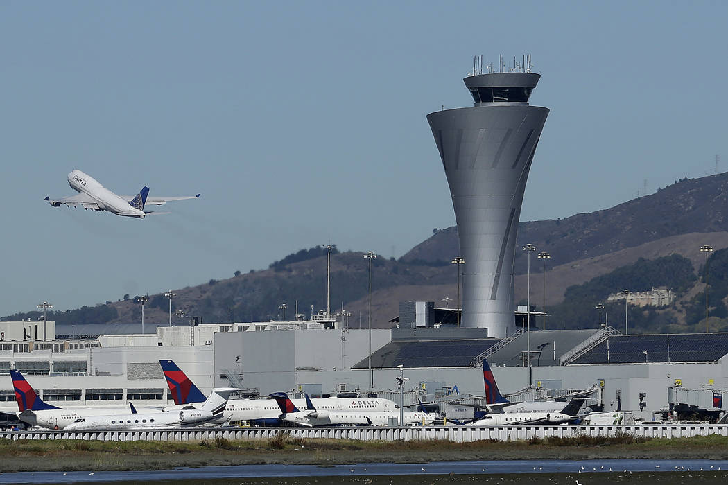 Air traffic control tower is in sight as a plane takes off from San Francisco International Airport in San Francisco on Oct. 24, 2107. (AP Photo/Jeff Chiu, File)