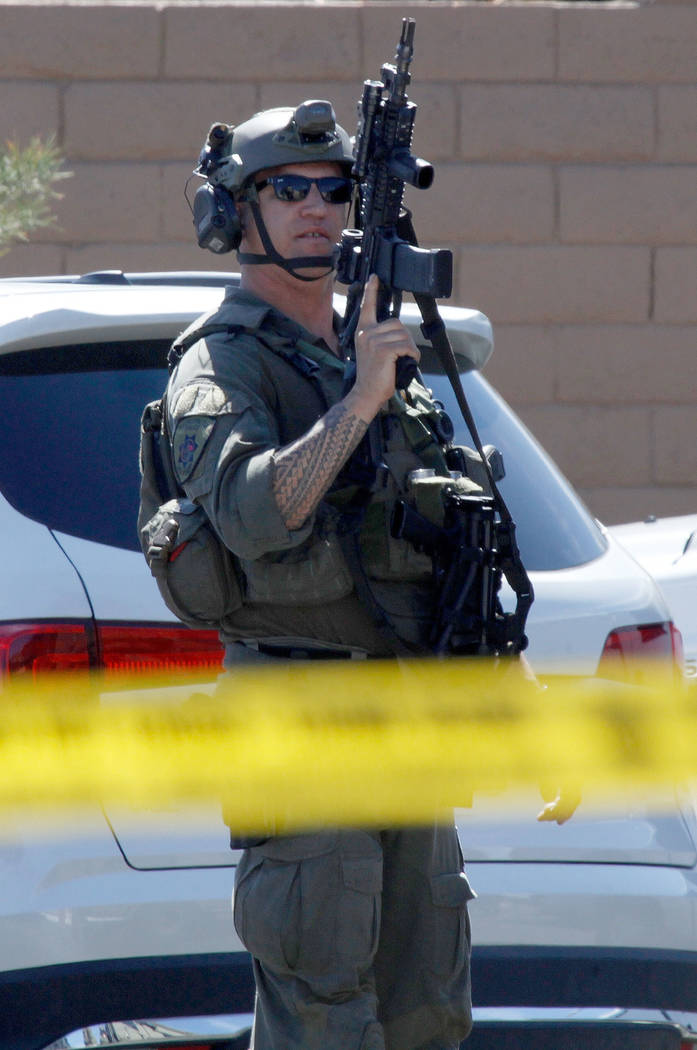 A Metropolitan Police Department SWAT team member stands with a gun during a barricade situation near Grand Teton and Durango in the northwest area of the Las Vegas valley, Saturday, March 23, 20 ...