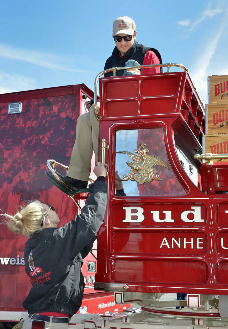 Handlers Lauren Lambeth, left, and Andrew LaCrosse polish the brass on the beer wagon during a visit by the Budweiser Clydesdales to the Smith's Marketplace at 9710 W. Skye Canyon Park Driv ...