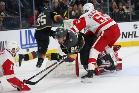 Vegas Golden Knights left wing William Carrier (28) is taken down by Detroit Red Wings defenseman Danny DeKeyser (65) during the first period of an NHL hockey game at T-Mobile Arena in Las Vegas, ...