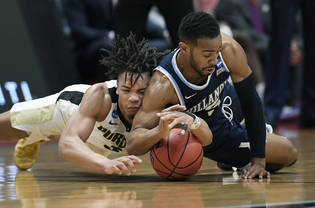 Purdue's Carsen Edwards, left, and Villanova's Phil Booth dive for a loose ball during the first half of a second round men's college basketball game in the NCAA tournament, Saturday, March 23, 20 ...