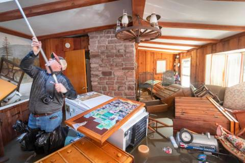 Steve O'Donnell works to open a skylight while standing in floodwaters inside a home Friday, March 22, 2019, in Bellevue, Neb. Flooding in Nebraska has caused an estimated $1.4 billion in damage. ...