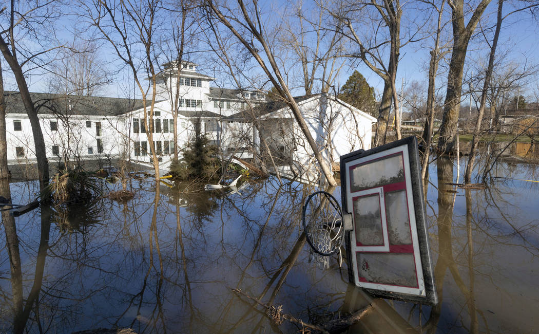 A wayward basketball hoop is seen behind a flooded home Friday, March 22, 2019, in Bellevue, Neb. Flooding in Nebraska has caused an estimated $1.4 billion in damage. The state received Trump's fe ...