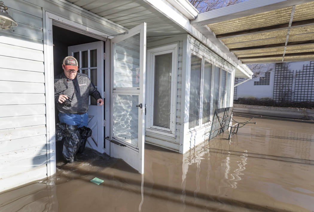 Steve O'Donnell exits his parent's flooded lake house in the Hanson's Lake area Friday, March 22, 2019, in Bellevue, Neb. Flooding in Nebraska has caused an estimated $1.4 billion in damage. The s ...